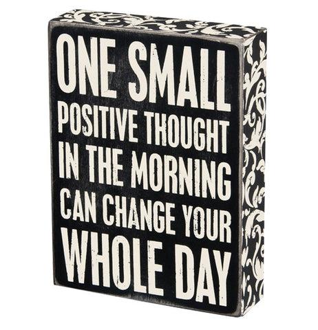 "The ""Positive Thought"" Box Sign contains white letters that say ""One small positive thought in the morning can change your whole day"" over a black background with decorative florid patterns on the sides."