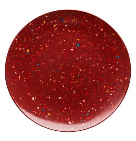 This dark red plate teems with white paint splattered polka dots.