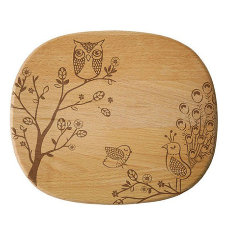 A cheese board beechwood that has etchings with a owl perched, peacock and sparrow.