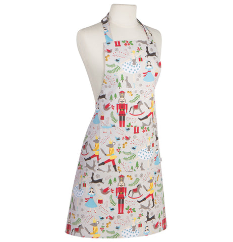 This white cooking apron features a design of different nutcracker characters, such as black deer outlines, red toy soldiers, rocking horses, mouse king designs, gray rabbits, and women in blue dresses.