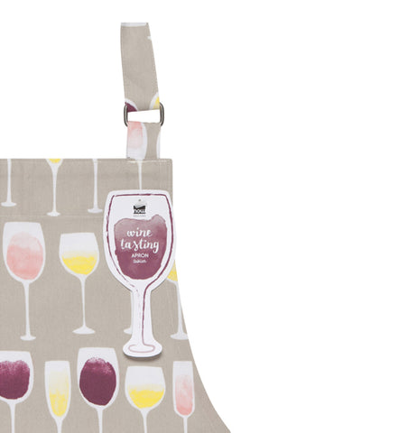 "Close up of the corner of the ""Wine Tasting"" Apron and shows several different wine glasses on a gray background and a tag shaped like a wine glass attached to the adjustable strap."