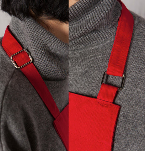 Someone wearing the red  Chef Apron with an adjustable neck strap.