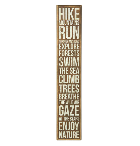 "This long and thin brown box sign says the words, ""Hike Mountains - Run Through Meadows - Explore Forests - Swim The Sea - Climb Trees - Breathe The Wild Air - Gaze At The Stars - Enjoy Nature"" in white lettering."