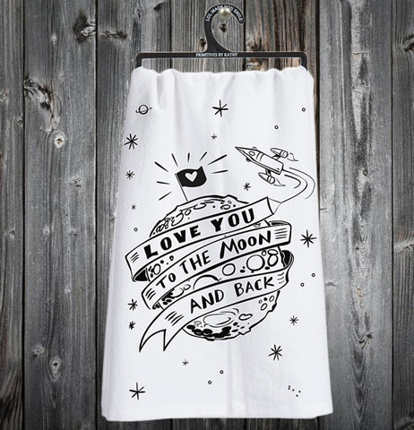 "The white dish towel with the words, ""Love You to The Moon and Back"" in black print with a rocket wrapping the moon with a black flag at the top with an outlined heart and around the moon there are various sizes of ""stars"" is shown here hanging from a nail against a dark grey wall."