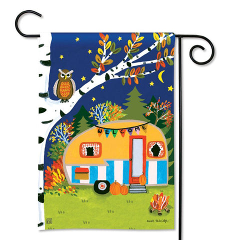 This Autumn themed flag features a trailer camped out under the stars next to a white tree with an owl sitting in it. A campfire is shown burning next to the trailer.