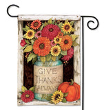 "This turquoise mason jar vase with orange, magenta, and yellow flowers in it says, ""Give Thanks Always."" in black lettering. Some sunflowers and an orange pumpkin sit next to the jar."