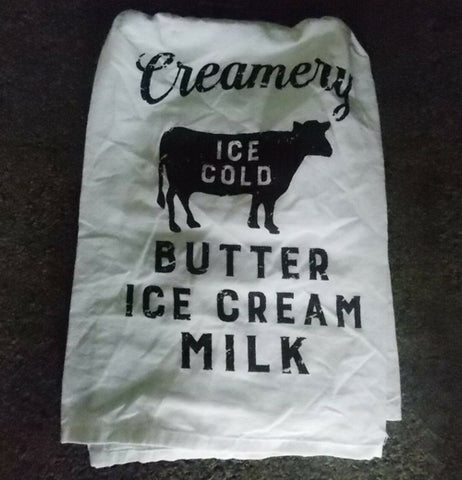 The white towel with the black cow and ice cream words is shown lying on a black background.