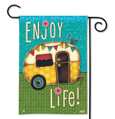"This garden flag says, ""Enjoy Life"" in white lettering with a yellow, white, red and brown trailer and with a multi-colored banner of flags. The background is blue and green."