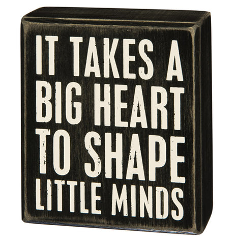 "This small black wooden box depicts the words, ""It Takes A Big Heart To Shape Little Minds"" in its center."