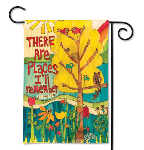 Colorful garden flag with birds sitting in a yellow tree behind red, orange, yellow, and green flowers with There Are Places I'll Remember written in red next to the tree on a black flag pole.