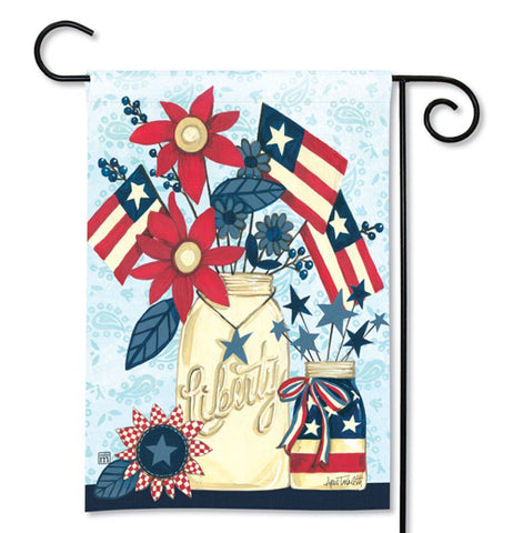 "This blue garden flag held up by a black metal hanger sports a design of American flags and red flowers sticking out of a jar with a blue star necklace. The word, ""Liberty"" is spelled out on the jar. A smaller jar is shown with an American flag wrapped around it."