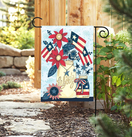 The garden flag with the American flag design on it is shown hanging from its hanger in front of a wooden fence.