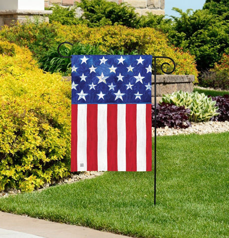 The American flag style garden flag is shown sitting on a lawn.