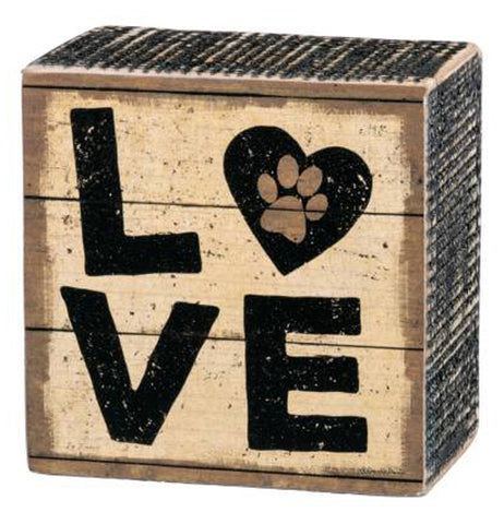 "Rustic looking square, wood box sign with black capital letters 'L' and 'O' above the letters 'V' and 'E'. The ""O"" is the shape of a heart with a brown paw print in the center. The tan background and black ridged sides have a distressed painted look."