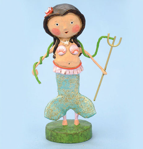 The figurine of the girl in the mermaid outfit is shown against a blue watery background.