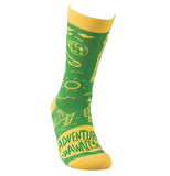 "This green sock with a yellow top, heel, and toe sports a design of different items, such as a camper, a fishing hook, a boat, and the sun. A yellow square sits at the bottom with the words, ""Adventure Awaits"" in green lettering."
