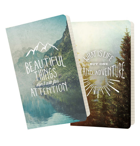 "These are two large sized notebooks, one depicting a lake in the mountains saying, ""Beautiful Things Don't Ask for Attention"", the other depicting a forest saying, ""Life is One Grand Adventure""."