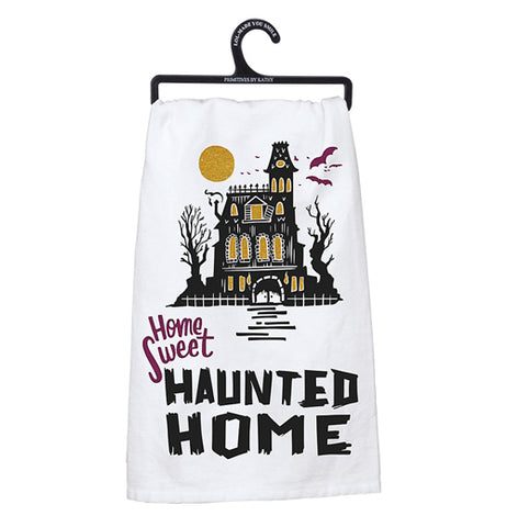 "White dish towel with a black mansion that has glittery gold windows with a glittery gold moon and purple bats above. The words ""Home sweet"" are printed in purple and the words ""Haunted Home"" are printed in bold black letters underneath the mansion."