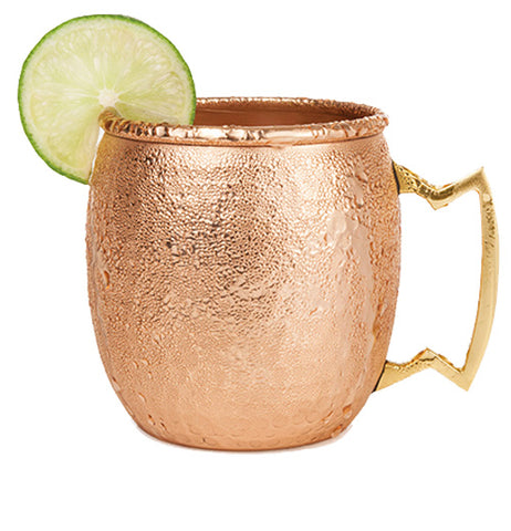 One hammered copper mule mug with a brass handle and a lime slice on the rim.
