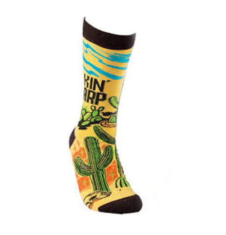 "This yellow and orange sock with a black top, heel, and toe has a picture of a desert with green cactus and blue sky. Above the cactus are the words, ""Lookin' Sharp"" in black lettering."