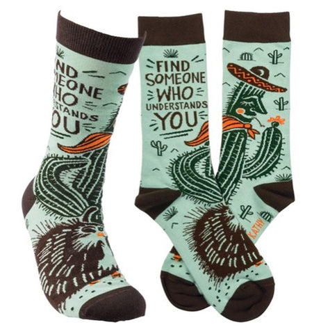 The green socks with the cactus and porcupine are shown from the side and front angles.