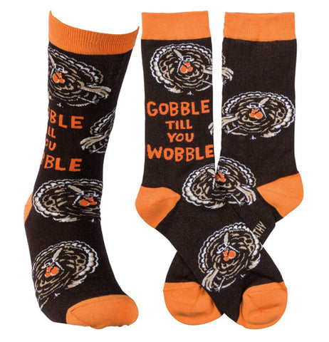 "This image shows the socks from three different angles. The first shows the sock from the front. The second shows the side of the sock with the words, ""Gobble Till You Wobble"" sewn against its black background. The third shows the orange and white turkeys against its black background."