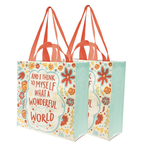 "Two ""Wonderful World"" Market Tote Bags stand next to each other featuring red words that say, ""And I Think to Myself What a Wonderful World"" with a red, blue, yellow, and orange floral design with a blue globe."