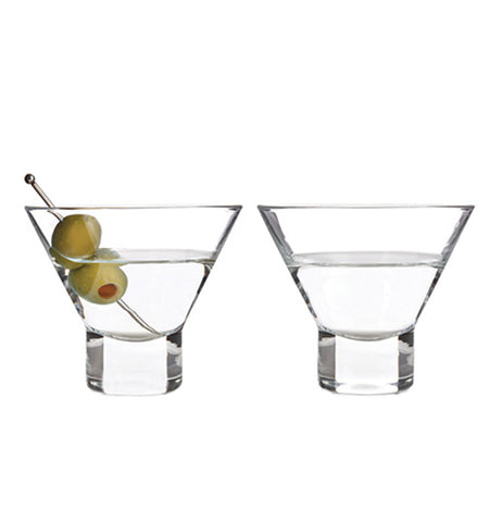 Two clear stemless martini glasses half full with a clear liquid, one has a cocktail pick with two green olives. The glasses are sitting next to each other on a white background.