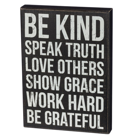 "That ""Follow Christ"" Box Sign features white block words which say, ""Be Kind, Speak Truth, Love Others, Show Grace, Work Hard, Be Grateful"" over a black background."