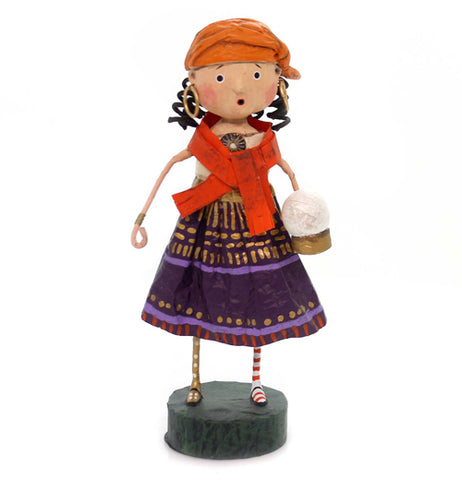 This figurine is of a girl in a fortune teller costume with gold, purple, and red dress, holding a crystal ball.