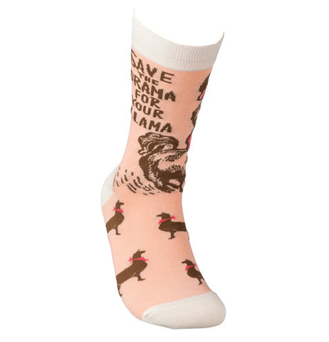 "These socks are a light salmon pink with brown llamas wearing red scarfs and hats all around and at the top of the socks. Below the cream colored top are the words, ""Save the Drama for Your Llama""."