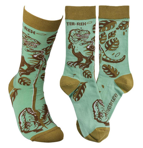 "The teal green socks with the taupe tops, heels, and toes are shown with fern and tea plants along with a picture of a T-Rex. The words, ""Tea Rex"" are at the top of the socks in brown lettering."