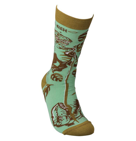 "This teal green sock with a taupe top, heel, and toes has a design of a Tyrannosaurus Rex and tea plants. The words, ""Tea Rex"" are written at the top of the sock in brown lettering."