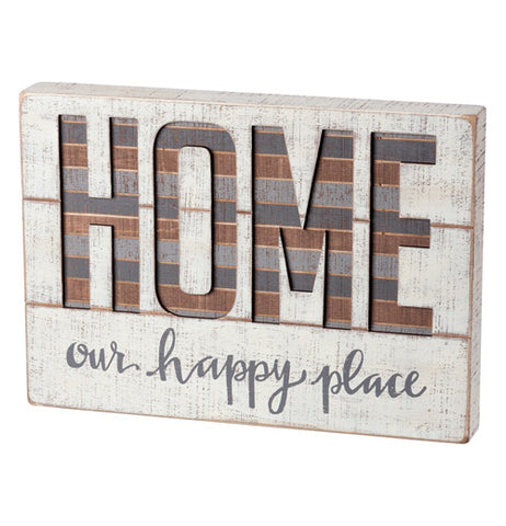 "This cream colored wooden block displays the word ""HOME"" stenciled in the center with the words, ""our happy place"" written in gray underneath."