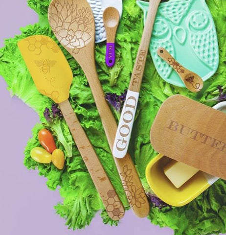 The yellow spatula with the bumblebee picture on its head is shown mixed with other spoons and spoon holders all sitting on grass.