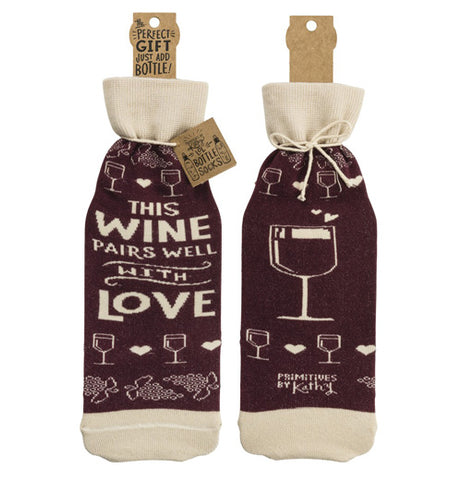 "The ""Pairs Well"" bottle cover has text that reads ""This Wine Pairs Well With Love"" in white text over a purple background on the front and an illustration of a wine glass over a purple background on the back."