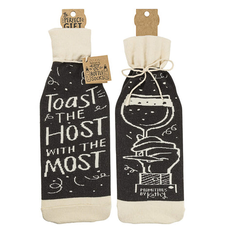 "This black and white cloth wine bottle cover features the words, ""Toast the Host with the Most"" in white lettering on one side, and a picture of a hand raising a wine glass on the other."