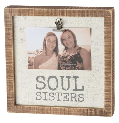 "This wooden box frame holds a clipped on picture of two women with the words, ""Soul Sisters"" below them in gray lettering against a cream colored background."