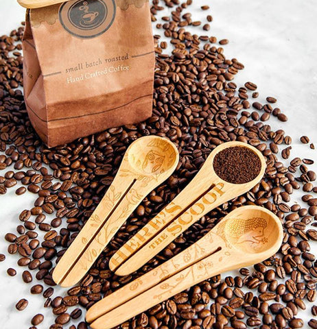 The coffee scoop with the picture of the owl is shown next to two other wooden spoons with similar designs. The three spoons sit on some coffee beans which sit next to a bag.
