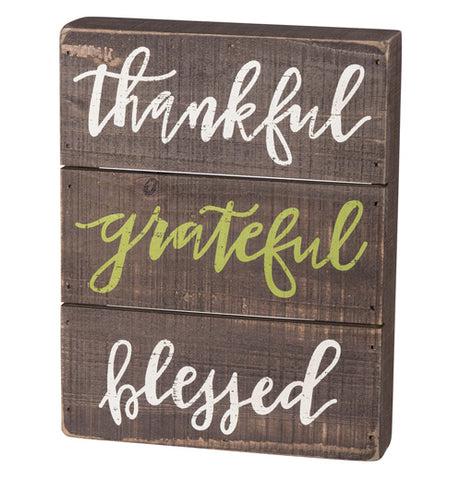 "The ""Thankful"" Slat Box Sign shows the three words, ""Thankful, Grateful, Blessed"" in white and green cursive letters over a brown wooden background."