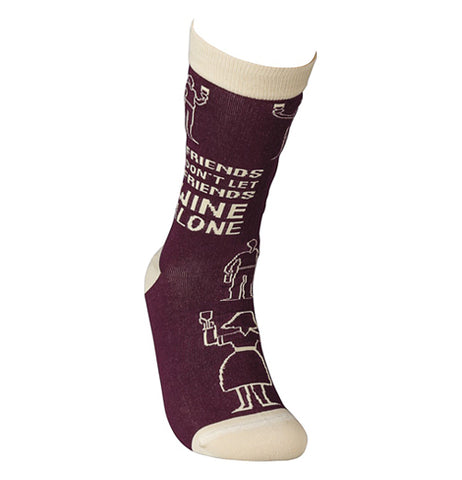 "One of the ""Wine Alone"" socks is on a mannequin foot."
