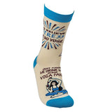 "This white sock with a blue top, heel, and toes has a picture of a woman pouring a bottle of wine into a glass. Above her are the words, ""Just Kidding We Drink Wine in Our Yoga Pants"" in brown lettering."