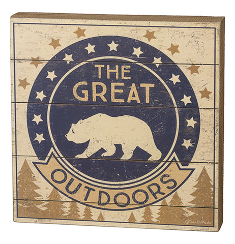"This small wooden box sign depicts a navy blue circle with a bear's outline. Around the circle are white and bronze colored stars against its beige background. The words, ""The Great"" are seen written in beige lettering while the word, ""Outdoors"" are written in black. Pine trees are shown in brown below the black and white bear symbol."