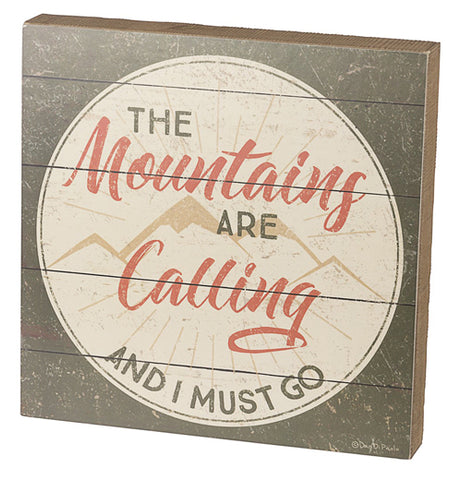 "This small silver wooden box depicts the words, ""The Mountains Are Calling And I Must Go"" in its center with a cream colored and golden brown outlines of mountains behind the words. The words, ""Mountains"" and ""Calling"" are written in orange red lettering, while the rest of the sentence is in grey lettering."