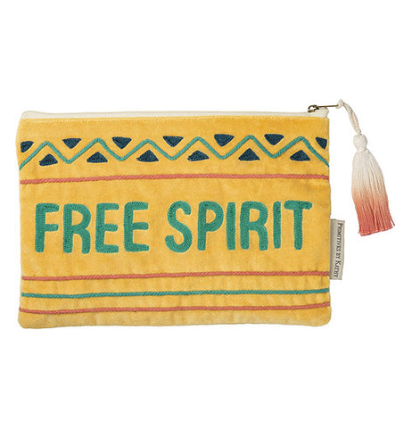 "The Pouch featured the words ""Free Spirit"" in green embroidered letter on a yellow background with orange, green, and black details along with a white and pink tassel."