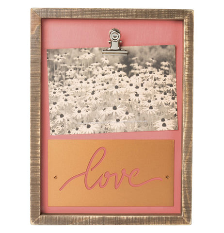 "This is a wooden box shaped work of art on a peach pink wooden background inside the frame. There is a clip in the center holding onto a black and white picture of sunflowers and underneath the picture is a copper metal sheet attached with the word ""Love"" in cursive letters cut out."
