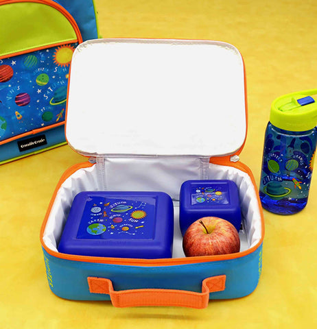 The solar system lunchbox is shown open with an apple and two food containers in it. A cup and backpack with the same planet design are shown on either side of the lunchbox.