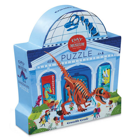 """Dinosaur Day at the Museum"" Puzzle kit packaged in a light blue museum box with Dinosaur displays and children looking at them."