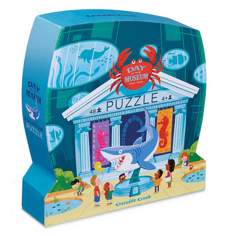 "The ""Aquarium Day at the Museum"" Puzzle kit has 48 pieces in a blue box that is shaped like a museum. It has the image of a museum with sea creatures displayed and children looking at the dispalys."