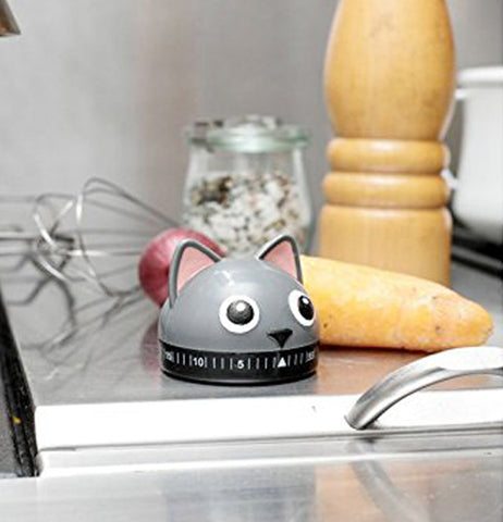 A Cat shape kitchen timer on a counter with a yam and a onion in the background.